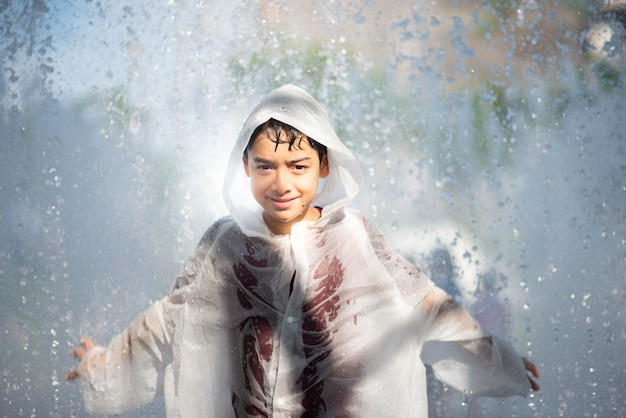 Der kleine junge, der wasser spielt, lässt brunnen unter dem stoff und dem regenschirm fallen