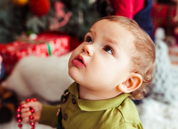 Der kleine junge, der weihnachtsbaum betrachtet
