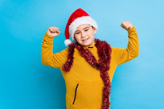 Der kleine junge, der weihnachtstag einen sankt-hut tragend feiert, lokalisierte das zeigen der stärkegeste mit den armen, symbol der weiblichen energie