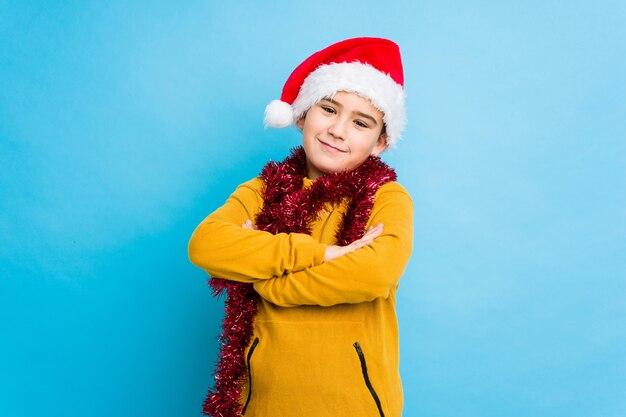 Der kleine junge, der weihnachtstag einen sankt-hut tragend feiert, lokalisierte, wer überzeugt sich fühlt und kreuzte arme mit entschlossenheit.