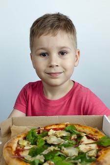 Der kleine junge in der küche aß sehr eifrig eine kleine pizza.