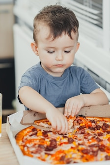 Der kleine junge isst selbst in der küche eine riesige schädliche pizza und trinkt saft, sehr fett und schädlich
