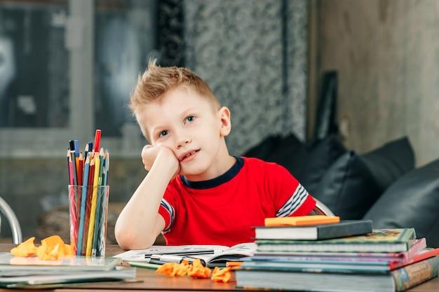 Der kleine junge ist traurig und gelangweilt, hausaufgaben zu machen.