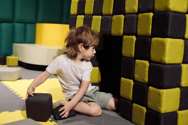 Der kleine junge konzentriert sich auf den bau eines hauses aus weichen spielblöcken, während er das kinderzentrum ausbildet. lernspiele. probleme der kinder. lernen durch spiel. arbeiten mit autismus.