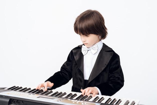 Der kleine junge lernt das spiel am synthesizer.
