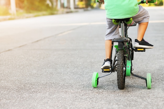 Der kleine junge lernt fahrrad fahren mit den stützrädern auf der straße.