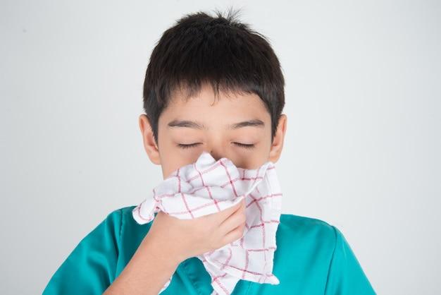 Der kleine junge niest und hustet von der grippe mit einem papiertaschentuch