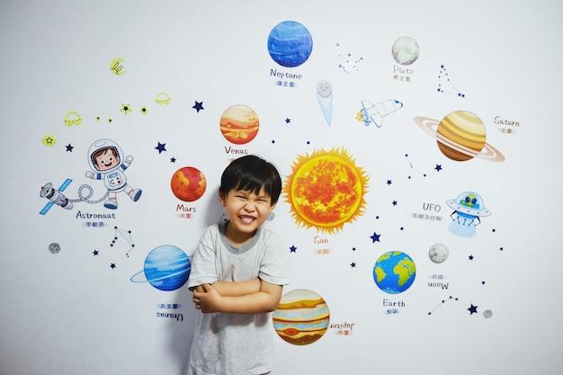 Der kleine junge stand lächelnd da, als er davon träumte, astronaut zu werden.