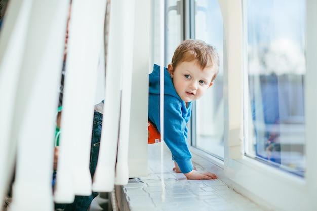 Der kleine junge steht in der nähe der fensterbank