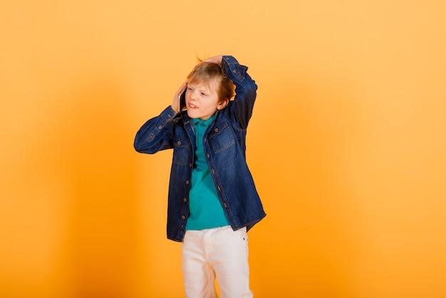 Der kleine junge telefoniert an der gelben wand