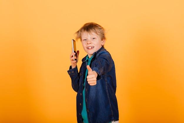 Der kleine junge telefoniert auf dem gelben hintergrund