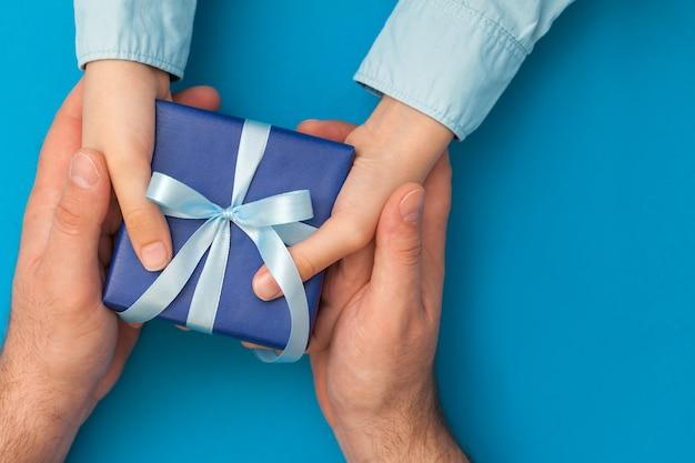Der kleine sohn gibt seinem vater eine geschenkbox