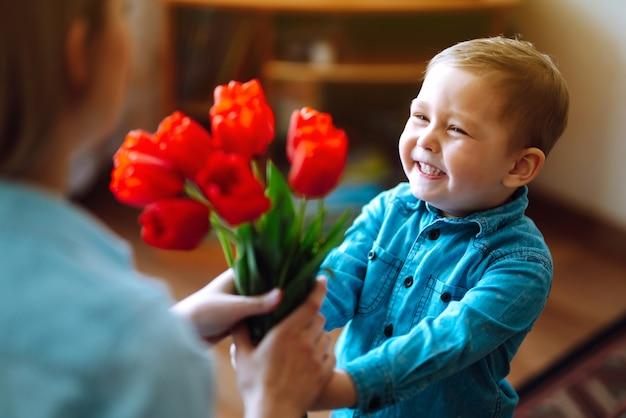 Der kleine sohn gratuliert der mutter und schenkt einen blumenstrauß tulpen. schönen muttertag.
