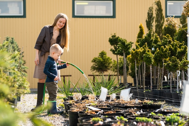 Der kleine sohn hilft mama, die pflanzentöpfe im gartencenter zu gießen
