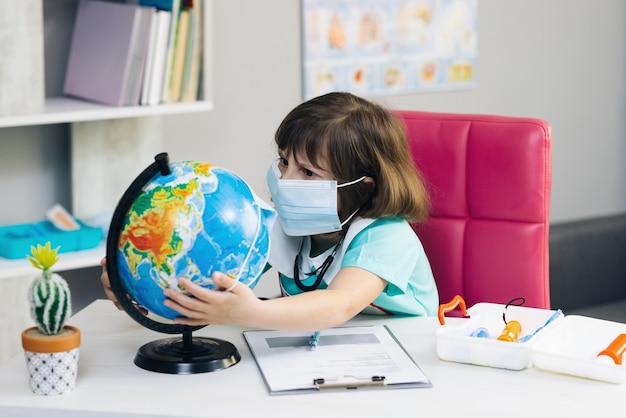 Der kleine süße kindermädchenarzt legt eine maske auf den globus des planeten erde, um die hände des erdplaneten zu retten