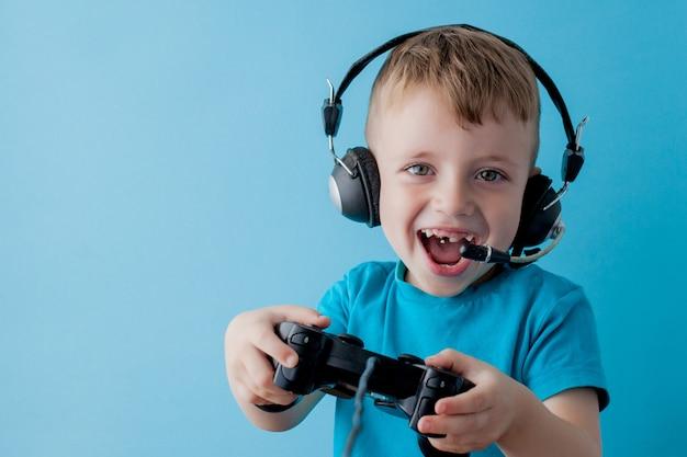 Der kleinkindjunge, der blaue kleidung trägt, halten in der hand steuerknüppel für gameson blau