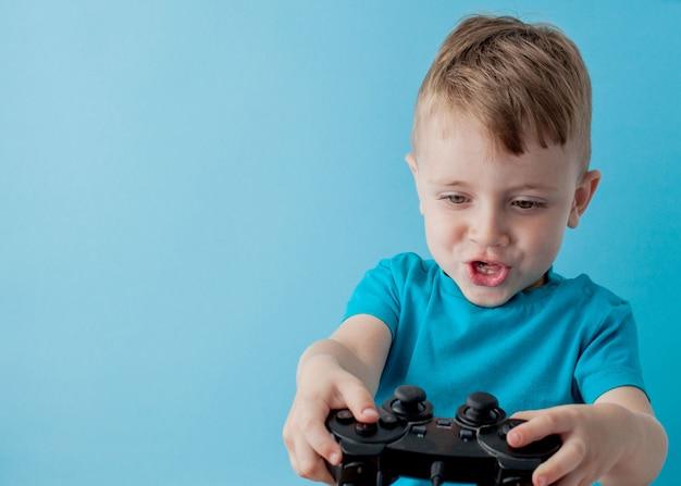 Der kleinkindjunge, der blaue kleidung trägt, halten in der hand steuerknüppel für spiele, kinderstudioporträt. leutekindheits-lebensstilkonzept. mock up kopie raum