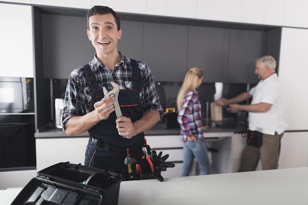 Der klempner posiert mit einem schraubenschlüssel in der küche.