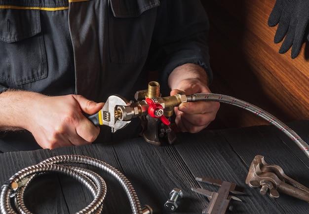 Der klempner verbindet die messingarmaturen mit einem verstellbaren schraubenschlüssel mit dem wasserhahn