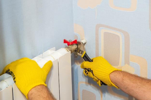 Der klempnermeister verbindet den wasserhahn mit einem verstellbaren schraubenschlüssel mit dem heizkörper