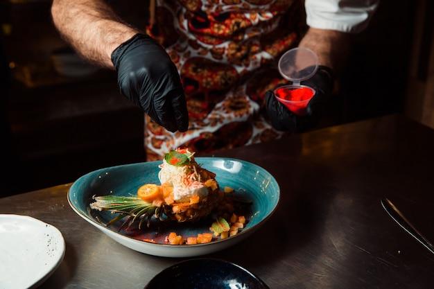 Der koch, dessen hände mit schwarzen handschuhen bekleidet sind, bestreut den gekochten salat, der in der hälfte der ananas liegt, mit roter würze.