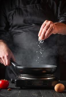 Der koch fügt salz hinzu, während er eier in einer pfanne kocht