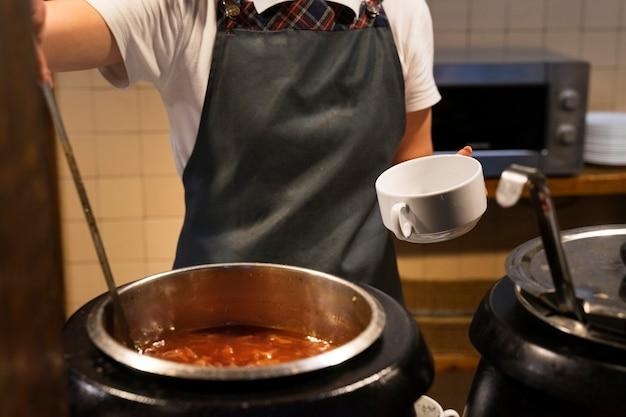 Der koch gießt borschtsch aus einem großen tank in einen teller