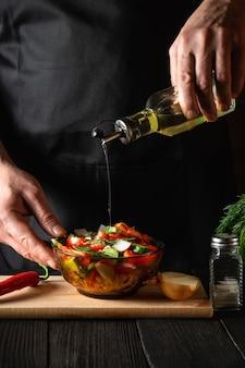 Der koch gießt olivenöl in eine schüssel salat. kochen sie leckeres und gesundes essen mit einer reihe von vitaminen