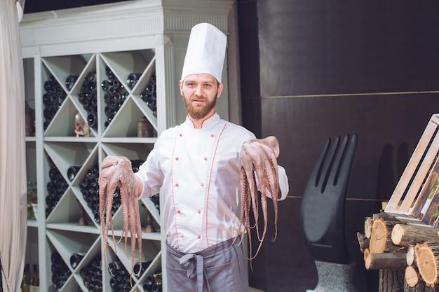 Der koch hält eine krake in der hand.