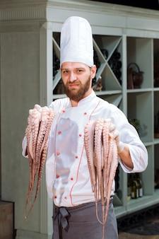 Der koch hält einen tintenfisch in der hand.