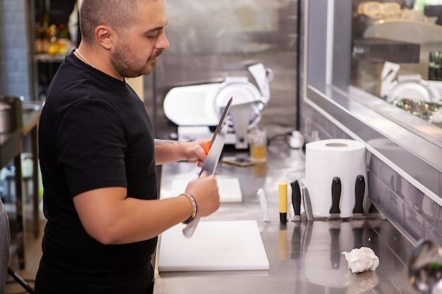 Der koch hält scharfe messer in den händen. vorbereitung zum kochen.