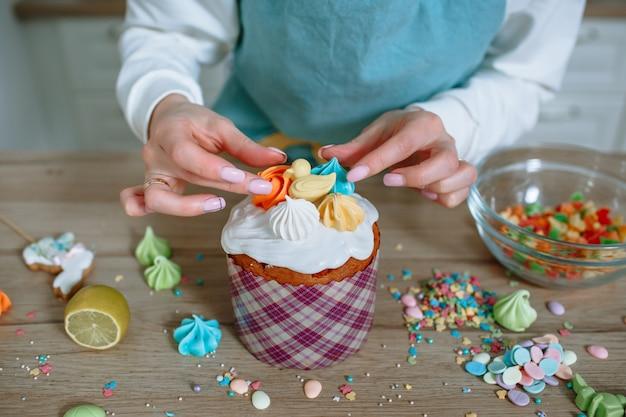 Der koch in der wohnküche setzt süße figuren auf das sahnehäubchen des osterkuchens