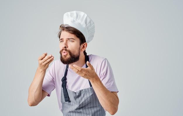 Der koch in einem grauen durcheinander und in einem rosa hemd gestikuliert mit seinen händen der emotionen. hochwertiges foto