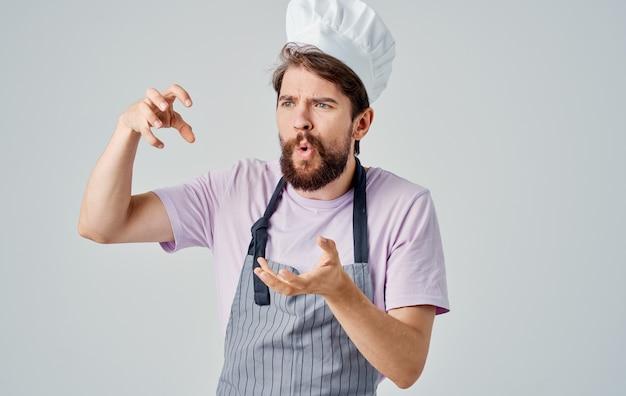 Der koch in einem grauen durcheinander und in einem rosa hemd gestikuliert mit seinen händen der emotionen.