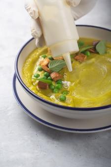 Der koch in handschuhen gießt aus einer weißen plastikflasche eine suppe aus püriertem bio-gemüse mit crackern, grünen erbsen und kräutern mit olivenöl. richtige ernährung, essen plattieren