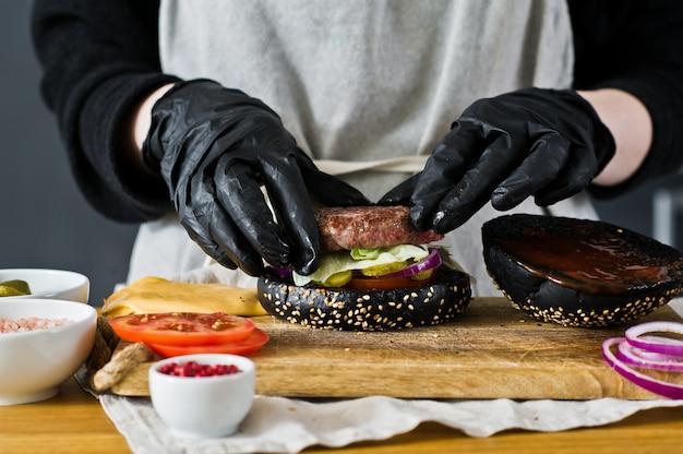 Der koch kocht einen cheeseburger. das konzept, einen schwarzen burger zu kochen. selbst gemachtes hamburgerrezept.