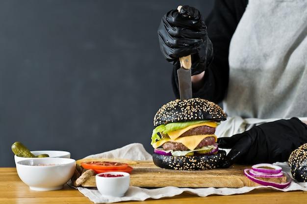 Der koch kocht einen saftigen burger. das konzept des kochens des schwarzen cheeseburgers. selbst gemachtes hamburgerrezept.