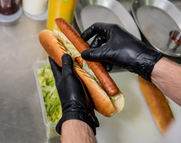 Der koch kocht hot dog auf einem grill. restaurant.