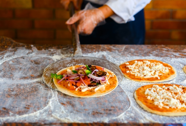 Der koch legt die pizza in den ofen.