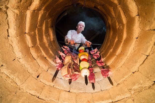 Der koch macht schaschlik auf einem tandoor.