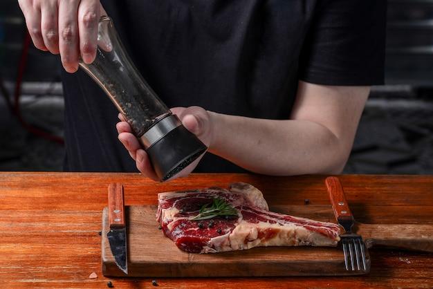 Der koch marinierte ein steak mit schwarzem pfeffer