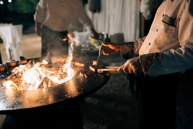 Der koch misst die temperatur des steaks mit einem thermometer auf dem grill
