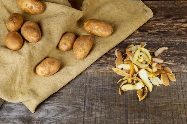 Der koch reinigt die kartoffeln mit einem messer