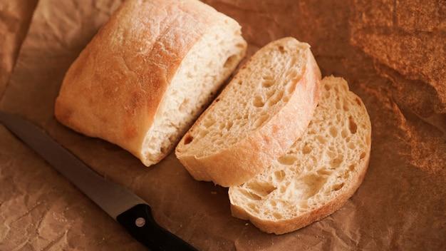 Der koch schneidet das ciabatta mit einem messer. ciabatta-scheiben auf kraftpapier. frisches leckeres gebäck. frisches hausgemachtes brot. gesundes essen
