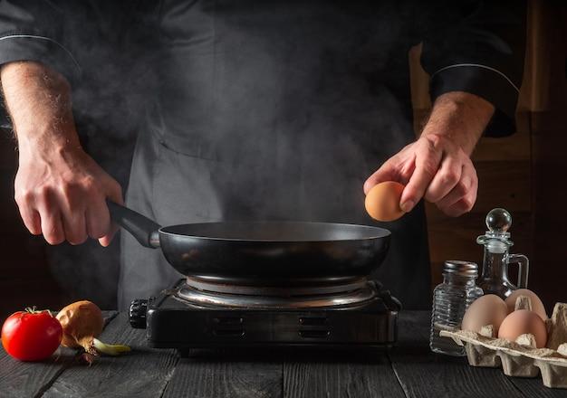Der koch versucht, ein ei auf einer bratpfanne zu zerschlagen, um ein köstliches frühstück zuzubereiten