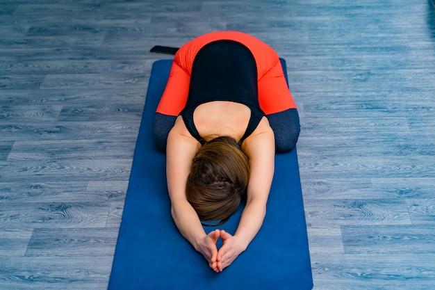Der körper der frau, der eine matte mit dem kopf unten liegt und während des trainings sich entspannt. junge sportliche frau in übendem yoga der sportkleidung und in handeln, übung im yogastudio atmend.