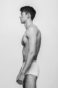 Der körper des mannes im profil auf dem weiß