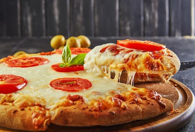 Der köstliche geschmack von pizza und käsescheiben mit mozzarella und tomaten. dreieckspizza mit stretchkäse und gewürzen