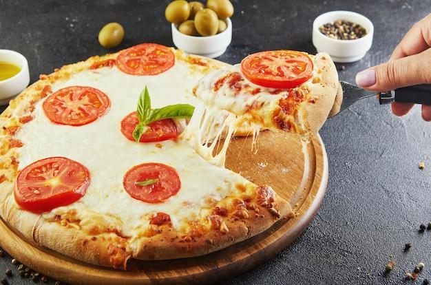 Der köstliche geschmack von pizza und käsescheiben mit mozzarella und tomaten.
