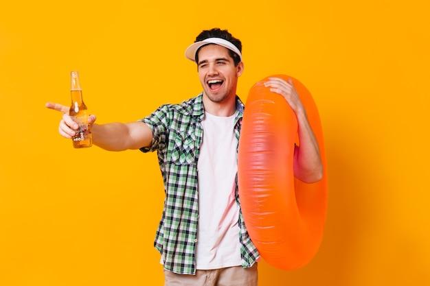 Der kokette mann in guter stimmung zwinkert und posiert mit einer flasche bier und einem aufblasbaren orangefarbenen kreis.